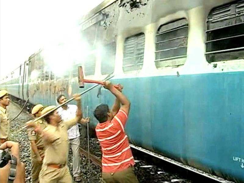 This video grab shows officials and rescue personnel trying to break into the car as smoke continues to smolder from the burnt out rail carriage after a fire ripped through a coach on a speeding express train near the town of Nellore. AFP Photo