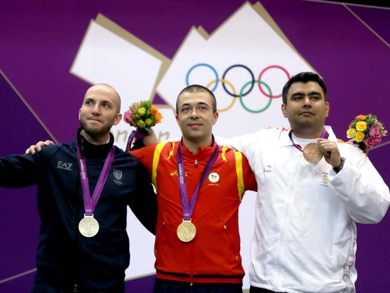 India's bronze Medallist Gagan Narang celebrates with Romania's gold medalist Alin George Moldoveanu and Italy's silver medallist Niccolo Campriani on the podium at the end of the men's 10m air rifle final during the London 2012 Olympic Games at the Royal Artillery Barracks in London ((AFP/Marwan Naamani)