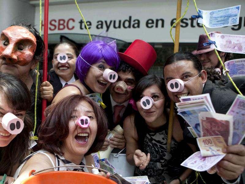 People, some displaying fake Mexican bills, pose for pictures as they demonstrate in front of the HSBC bank headquarters in Mexico City. AP Photo/Eduardo Verdugo