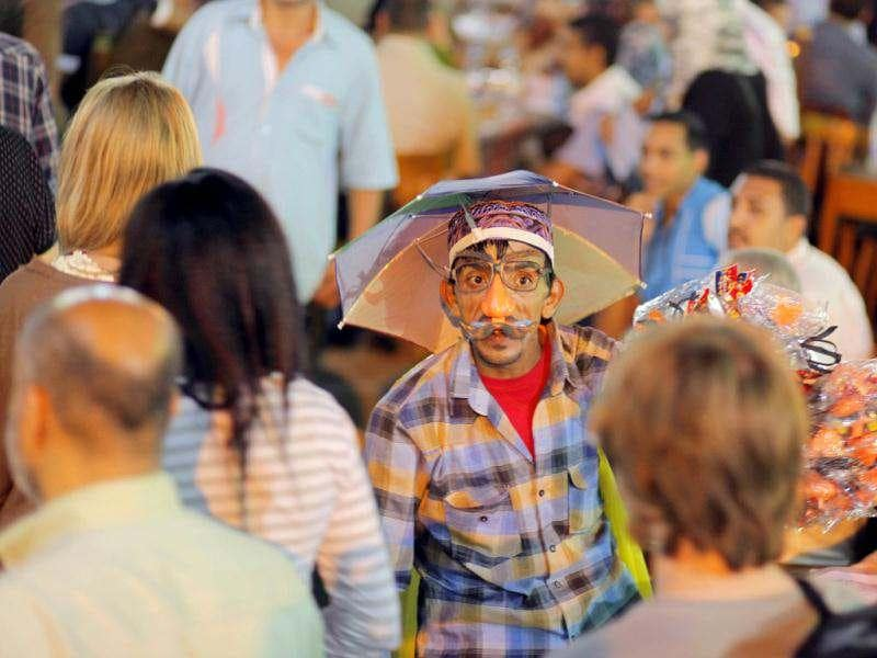 An Egyptian toys vendor chats with passing tourists at Al-Hussein historical site in Cairo, Egypt. AP Photo/Amr Nabil