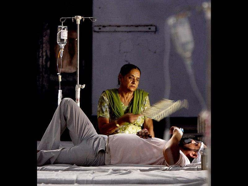 An attendant using a hand fan to aired patient in the ward of ENT hospital Amritsar during the Power Grid failure in several states of North and East India. HT/Munish Byala