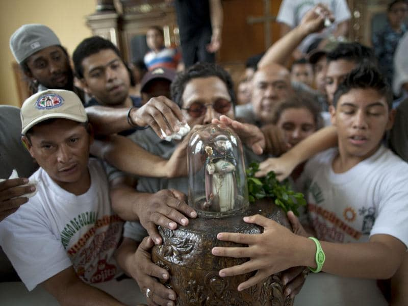 People touch an image of Santo Domingo de Guzman during celebrations at a church in Managua, Nicaragua. AP photo/Esteban Felix
