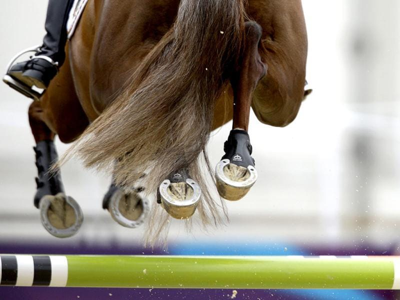 The hooves of Opgun Louvo, ridden by Sandra Auffarth, of Germany, clear a jump during the equestrian eventing individual show jumping at the 2012 Summer Olympics, in London. AP photo/David Goldman