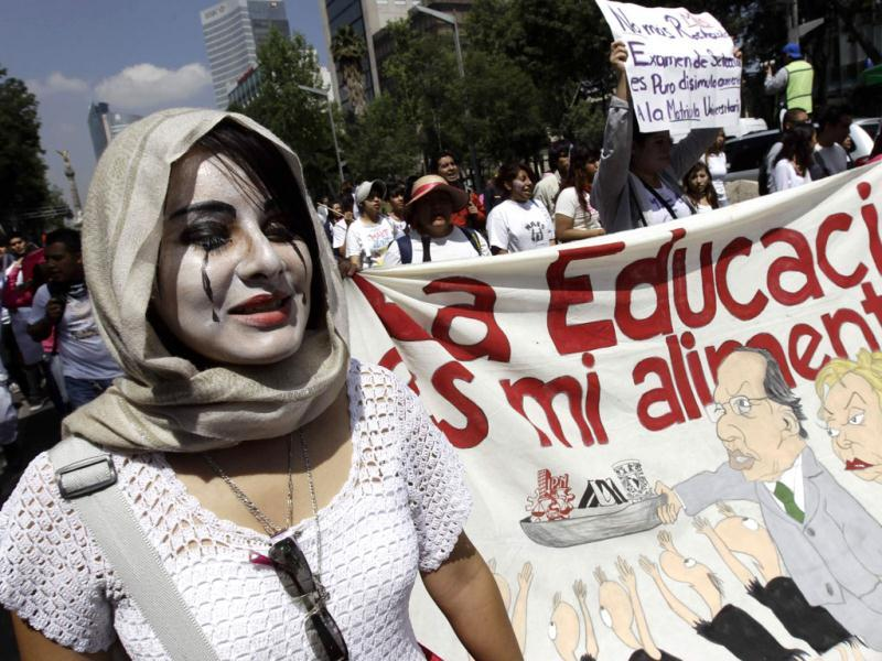 A student with her face painted holds a banner during a march along Reforma Avenue in Mexico City. Reuters photo/Henry Romero