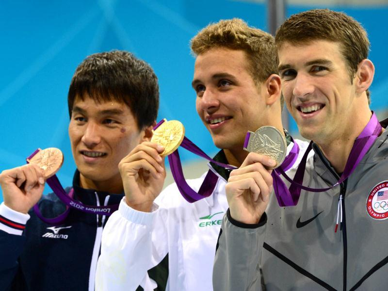 Gold medalist South Africa's Chad Le Clos (C), bronze medalist Japan's Takeshi Matsuda (L) and silver medalist US swimmer Michael Phelps (R) celebrate on the podium of the men's 200m butterfly final during the swimming event at the London 2012 Olympic Games in London. AFP photo/Christophe Simon