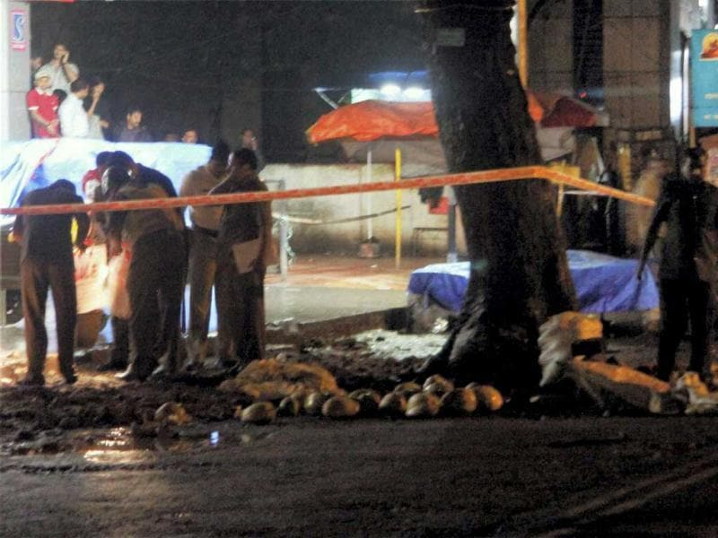 Policemen search for clues at a site of a blast in Pune on Wednesday. Five low-intensity bomb blasts in quick succession shook the city in the evening injuring at least two people. (PTI Photo/AP)