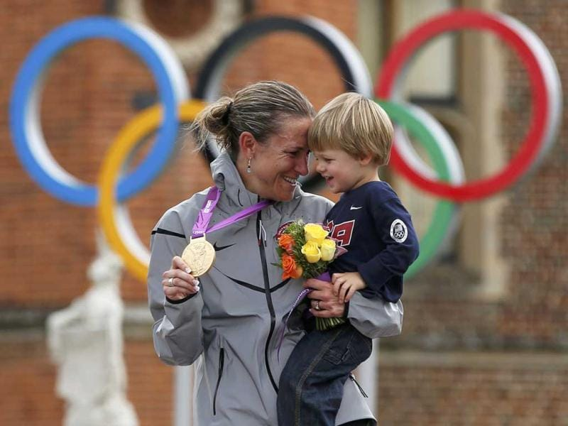 Gold medallist Kristin Armstrong of the US celebrates with her 22-month-old son Lucas William Savola on the podium during the victory ceremony of the women's cycling individual time trial at the London 2012 Olympic Games. Reuters/Paul Hanna