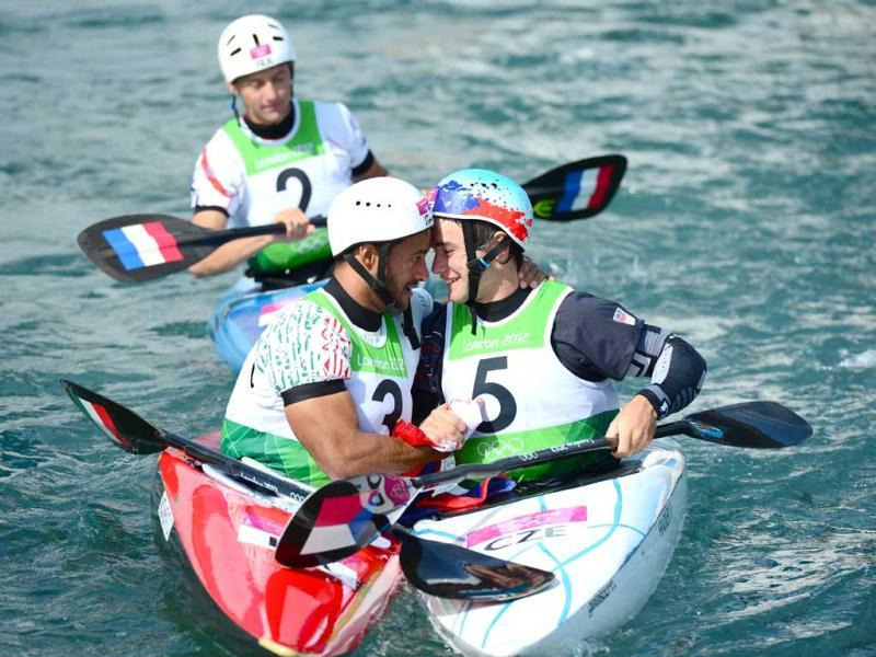 Gold medalist Italy's Daniele Molmenti is congratulated by silver medalist Czech's Vavrinec Hradilek next to France's Etienne Daille after winning the Kayak Single Men final at the