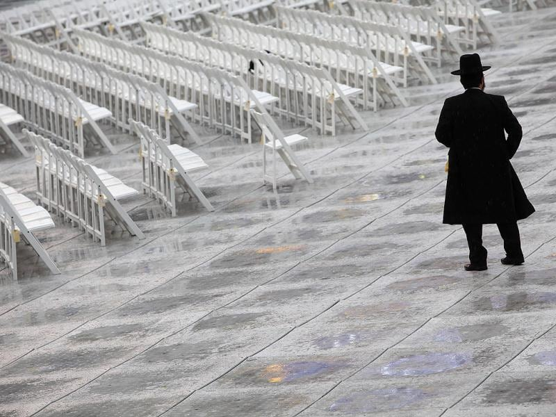 An Orthodox Jew stands near chairs as he arrives for the 12th Siyum Hashas, a celebration marking the completion of the Daf Yomi, a seven-year cycle of studying texts from the Talmud, the canon of Jewish religious law, at the MetLife Stadium in East Rutherford, New Jersey. Reuters photo/Eric Thayer