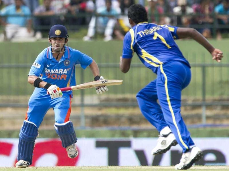 Gautam Gambhir (L) runs between wickets as Sri Lankan cricketer Thisara Perera (R) looks on during a fifth and final one-day international (ODI) match between Sri Lanka and India at the Pallekele International Cricket Stadium in Pallekele. AFP Photo/Ishara S Kodikara