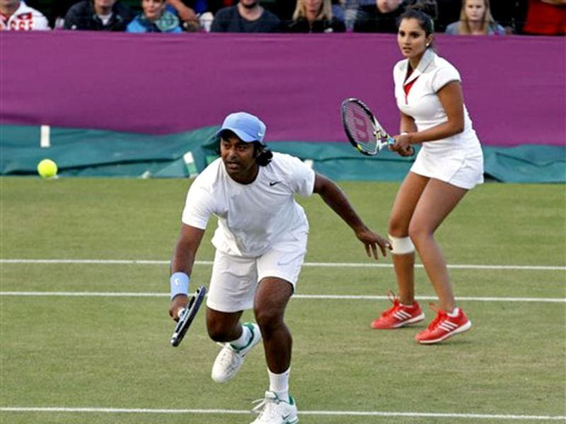 Leander Paes returns a shot as he plays a mixed doubles match against Victoria Azarenka and Max Mirnyi, with partner Sania Mirza at the All England Lawn Tennis Club at Wimbledon, in London, at the 2012 Olympics. AP Photo/Mark Humphrey