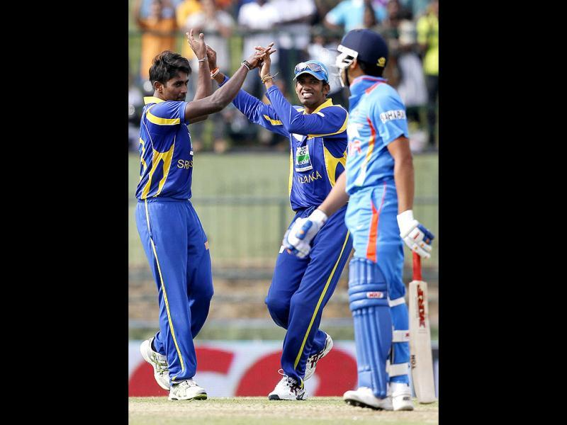 Sri Lanka's bowler Nuwan Pradeep (L) celebrates the dismissal of India's batsman Rohit Sharma (R) with Sachithra Senanayake (C) during their fifth one day international cricket match in Pallekele, Sri Lanka. (AP Photo/Gemunu Amarasinghe)