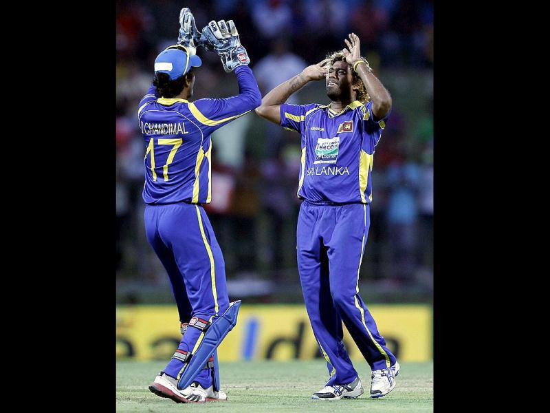 Sri Lanka's Lasith Malinga (R) celebrates with his team mate Dinesh Chandimal after taking the wicket of Mahendra Singh Dhoni (not pictured) during their final one-day international (ODI) cricket match in Pallekele. (Reuters/Dinuka Liyanawatte)