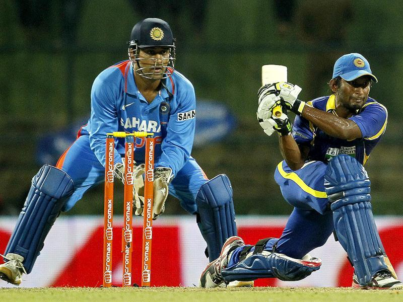 Sri Lanka's batsman Jeevan Mendis (R) bats as Mahendra Singh Dhoni (L) watches during the fifth one day international cricket match between India and Sri Lanka in Pallekele, Sri Lanka. (AP Photo/Gemunu Amarasinghe)