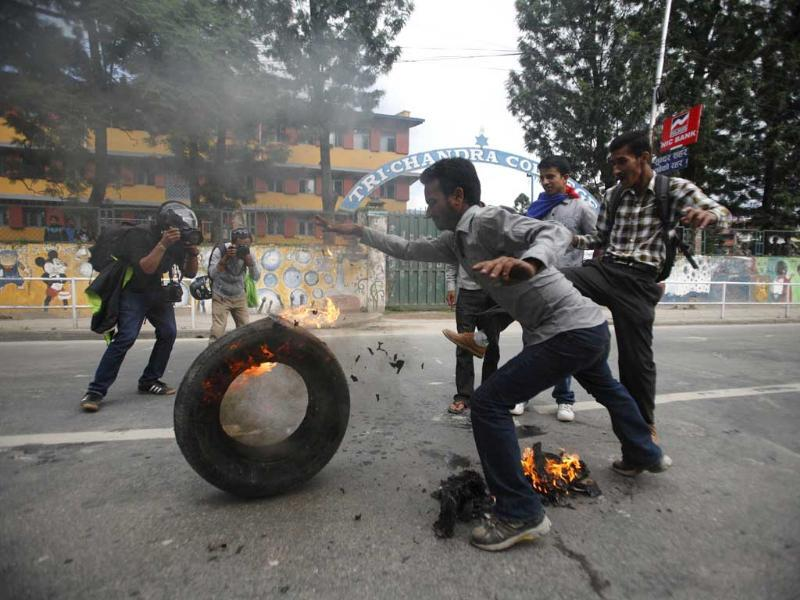 Activists of the Communist Party of Nepal Unified Marxist Leninist (CPN-UML) affiliated with Youth Association Nepal rolls a burning wheel during their general strike demanding the immediate resignation of Prime Minister Baburam Bhattarai in Kathmandu. Reuters/Navesh Chitrakar