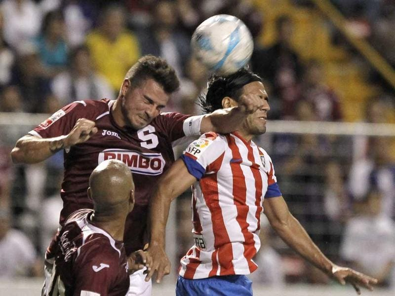 Radamel Falcao of Spain's Atletico Madrid jumps for the ball against Gabriel Badilla of Costa Rica's Deportivo Saprissa during their international friendly soccer match at the Ricardo Saprissa stadium in San Jose. Reuters/Juan Carlos Ulate