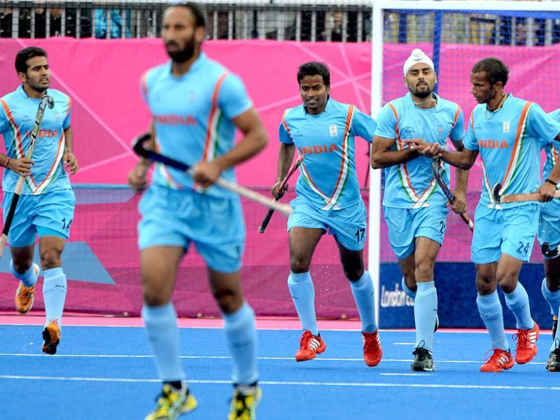 Teammates congratulate Gurwinder Singh Chandi (3R) during the men's field hockey preliminary round match between India and South Korea at the Riverbank Arena in London during the London 2012 Olympic Games. AFP Photo/Indranil Mukherjee