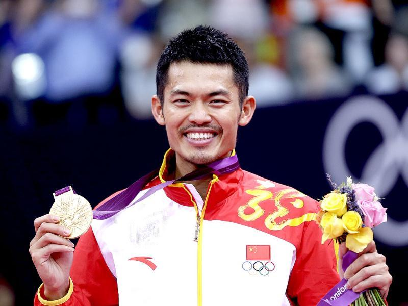 China's Lin Dan shows his gold medal after winning the men's singles badminton gold medal match of the 2012 Olympics in London. AP Photo/Saurabh Das