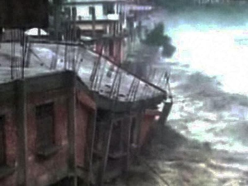 A TV grab shows houses being washed away in cloudbursts and floods in Uttarkashi. (PTI Photo)