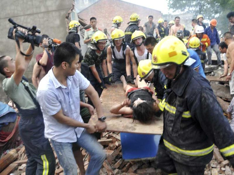 Rescuers carry a survivor from a collapsed house after an explosion rocked a family-owned workshop in a village in Wenzhou, Zhejiang province. (Reuters/UNI)