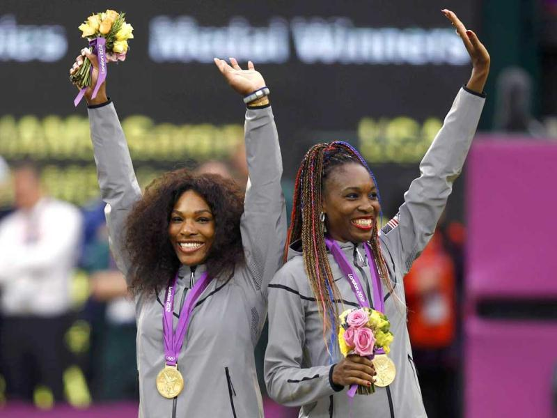 Serena Williams (L) and her sister Venus Williams, of the US, wave with their gold medals during the presentation ceremony for the women's doubles tennis at the All England Lawn Tennis Club during the London 2012 Olympic Games. (Reuters/UNI)
