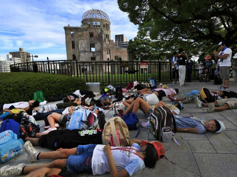 Students lie on the ground pretending to die in front of the Atomic Bomb Dome to mark the 67th anniversary of the atomic bombing in Hiroshima, western Japan. (AP/Vincent Yu)