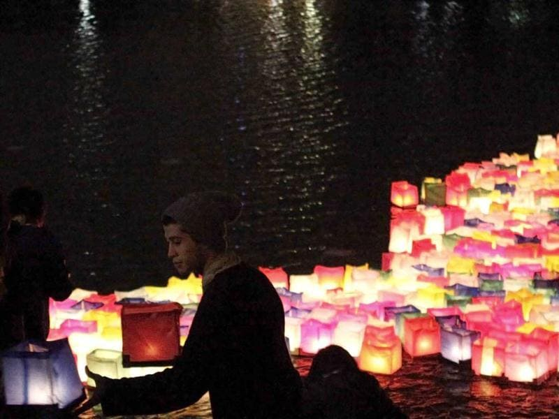 A man holds lanterns to place on a lake at Ibirapuera Park, to remember the 67th anniversary of the atomic bombings of the cities of Hiroshima and Nagasaki, in Sao Paulo. (Reuters/Nacho Doce)