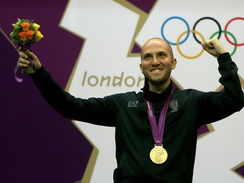 Italy's Niccolo Campriani, winner of the gold medal in the men's 50m rifle 3 positions final, stands on the podium at the London 2012 Olympic Games jubilates at the podium at the Royal Artillery Barracks in London. AFP photo/Marwan Naamani
