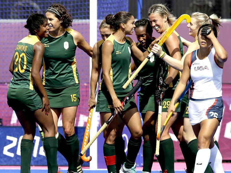 The United State's Kayla Bashore Smedley, right, walks to her position as South African players celebrate one of their seven goals during the women's preliminary match between USA and South Africa at the 2012 Summer Olympicsin London. South Africa won 7-0.(AP Photo/Bullit Marquez)