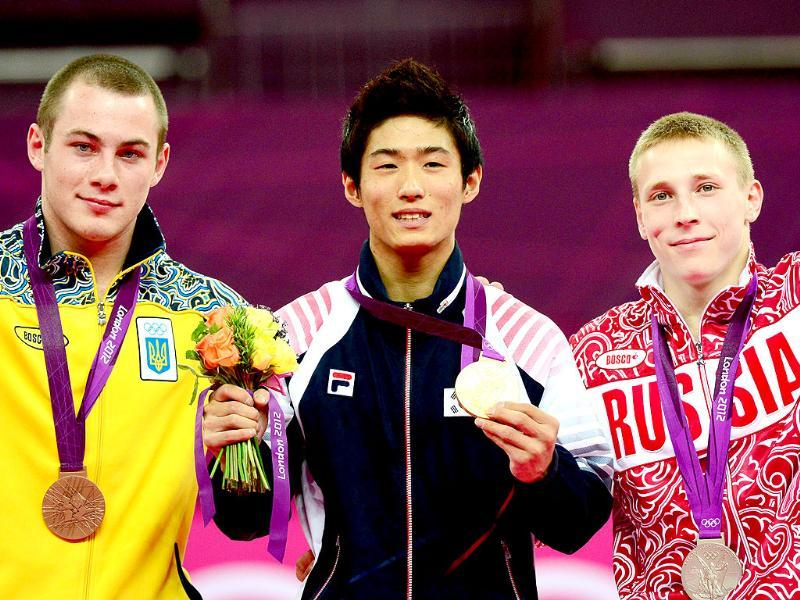 Gold medalist South Korea's gymnast Yang Hak Seon (C), silver medalist Russia's gymnast Denis Ablyazin (R) and bronze medalist Ukraine's gymnast Igor Radivilov celebrate on the podium of the men's vault of the artistic gymnastics event of the London Olympic Games at the 02 North Greenwich Arena in London. (AFP photo/Emmanuel Dunand)
