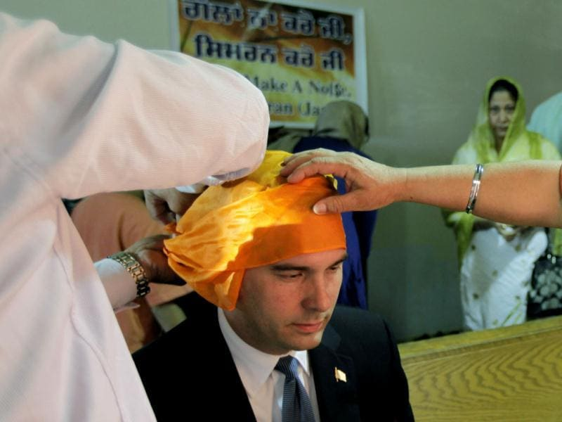 Wisconsin governor Scott Walker, is fitted with a head covering, by members of the Sikh community as he prepares to worship with them at the Sikh Religious Society of Wisconsin in Brookfield. AP/M Spencer Green
