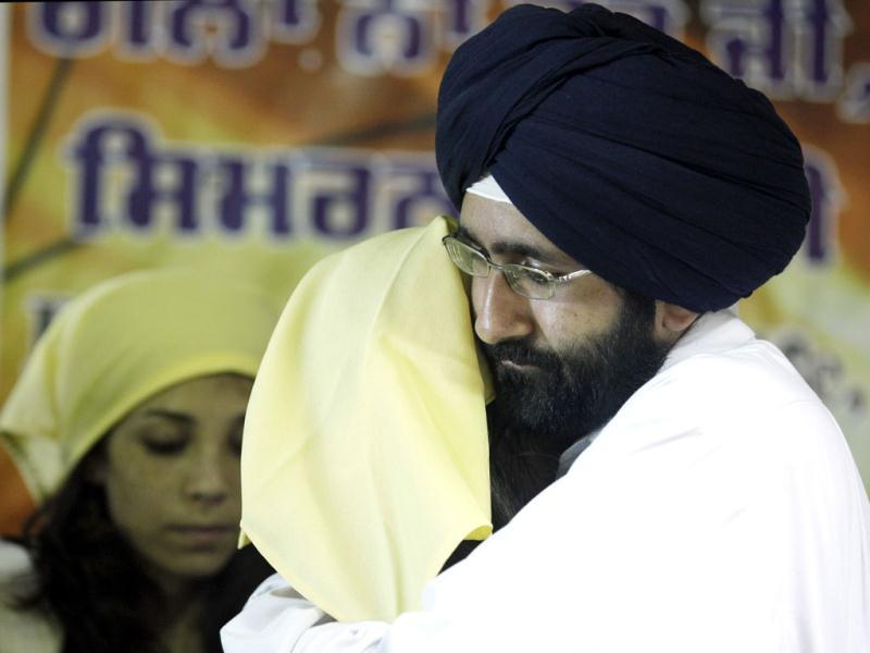 Worshipers in the Sikh community comfort each other as they prepare for a prayer service at the Sikh Religious Society of Wisconsin in Brookfield. AP/M Spencer Green