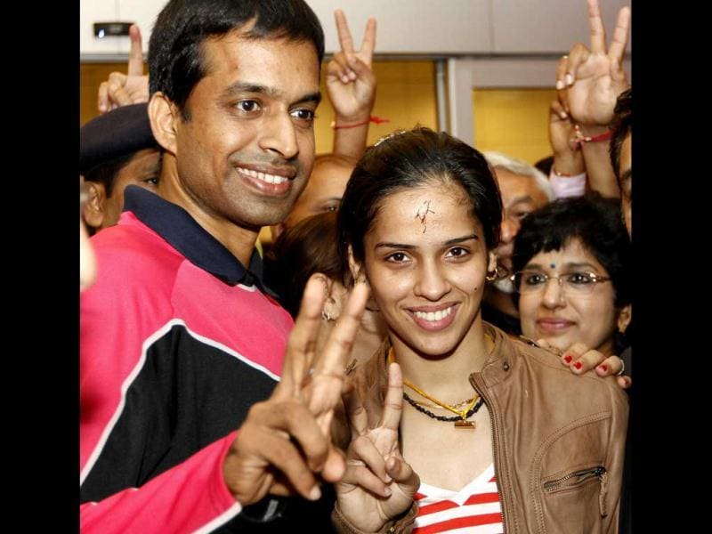 Saina Nehwal and her coach Gopichand (L) showing victory sign as they return from London at Indira Gandhi Airport in New Delhi. (Hindustan Times/Arijit Sen)