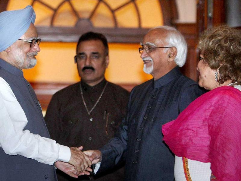 Prime Minister Manmohan Singh greets Mohammad Hamid Ansari after he was re-elected as Vice President of India, in New Delhi. Ansari's wife Salma is also seen. PTI/Vijay Kumar Joshi