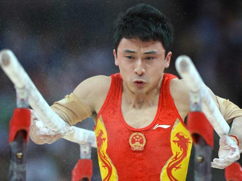 China's gymnast Feng Zhe performs to win gold in the men's parallel bars competition of the artistic gymnastics event of the London Olympic Games on August 7, 2012 at the 02 North Greenwich Arena in London. (AFP photo/Ben Stansall)