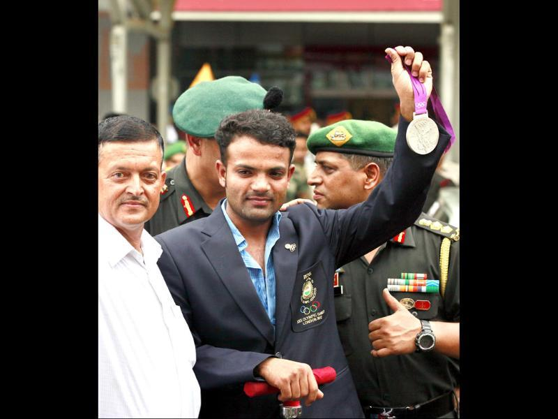 London Olympics 25-m rapid fire pistol silver medalist Subedar Vijay Kumar along with his father Banku Ram, accorded a rousing welcome by the Indian Army on his arrival at the Indira Gandhi International Airport. Raj K Raj/Hindustan Times