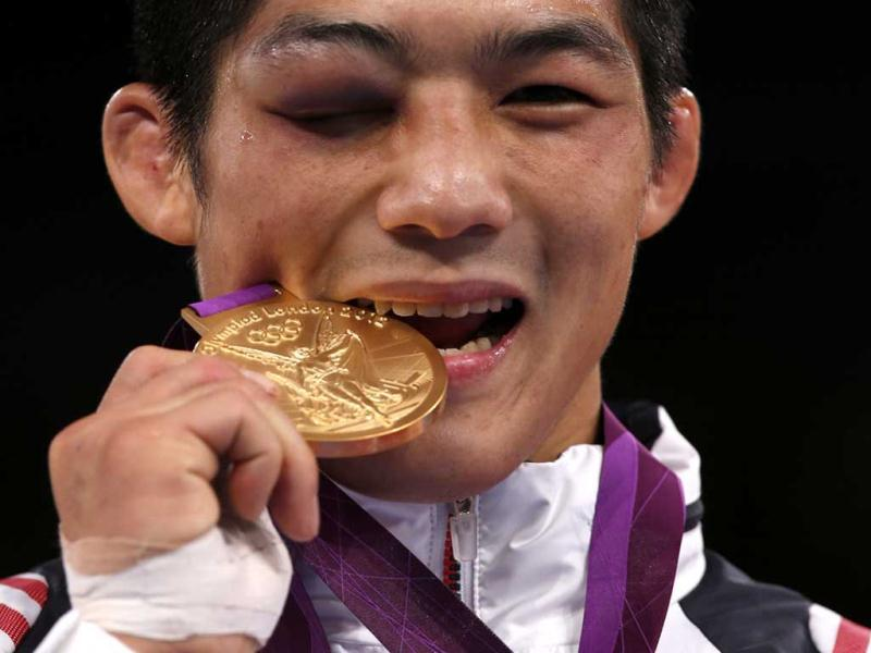 South Korea's Hyeonwoo Kim bites his gold medal at the podium of Men's 66Kg Greco-Roman wrestling at the ExCel venue during the London 2012 Olympic Games. Reuters photo/Damir Sagolj