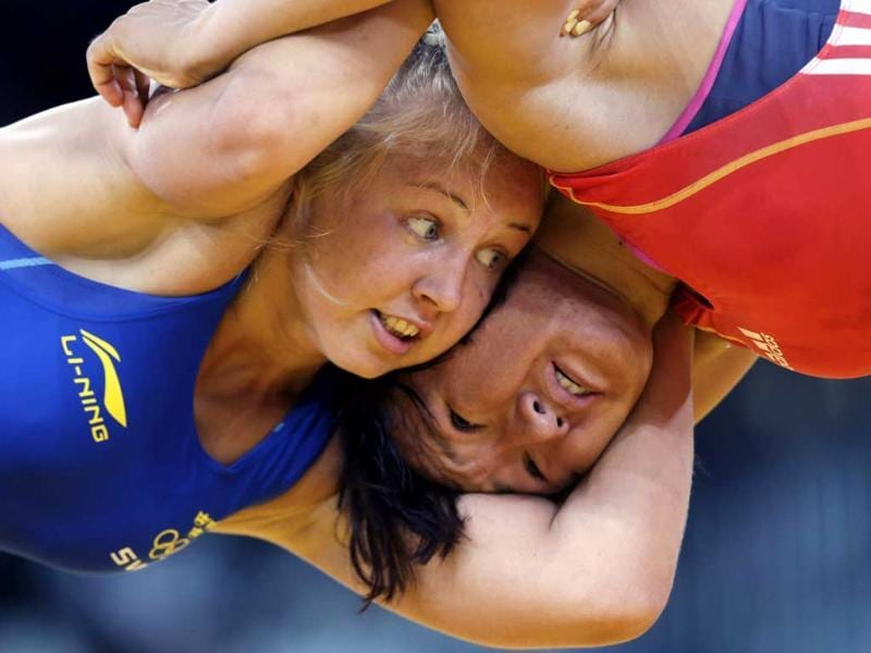 Henna Johansson of Sweden, left, and Aisuluu Tynbekova of Kygyzstan, compete in 63-kg women's freestyle wrestling at the 2012 Summer Olympics in London. (AP Photo/Paul Sancya)