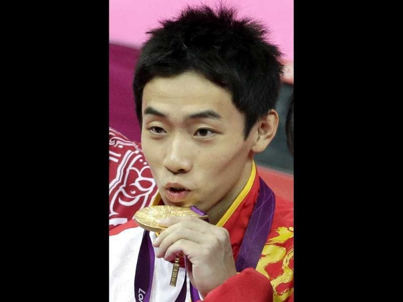 Chinese gymnast Zou Kai displays his gold medal for the artistic gymnastics men's floor exercise final at the 2012 Summer Olympics in London. (AP Photo/Gregory Bull)
