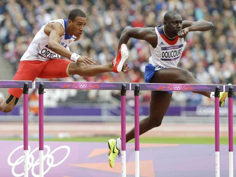 France's Ladji Doucoure, right, and Cuba's Orlando Ortega compete in a men's 110-meter hurdles heat during the athletics in the Olympic Stadium at the 2012 Summer Olympics, London. (AP Photo/Lee Jin-man)