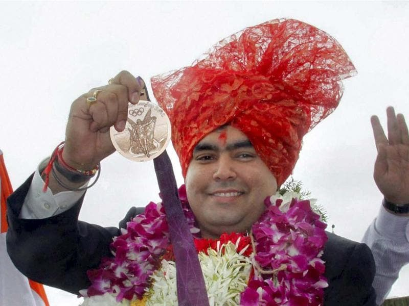 Olympic bronze medallist shooter Gagan Narang showing his medal as he is welcomed by his fans at Balewadi in Pune. PTI Photo