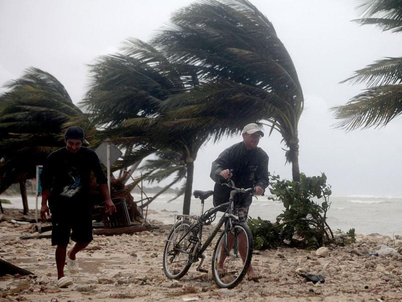 Residents walk past swaying palm trees following the passing of Hurricane Ernesto in Mahahual, in the Mexican state of Quintana Roo. Reuters Phhoto