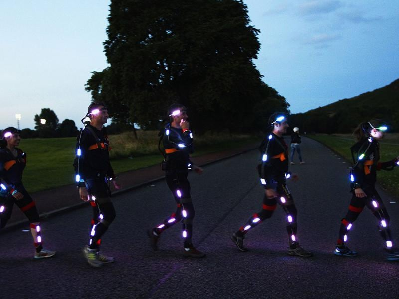 Runners taking part in NVA's Speed of Light walk across a path before taking part in the performance on Arthurs Seat during the Edinburgh International Festival in Edinburgh. Reuters photo