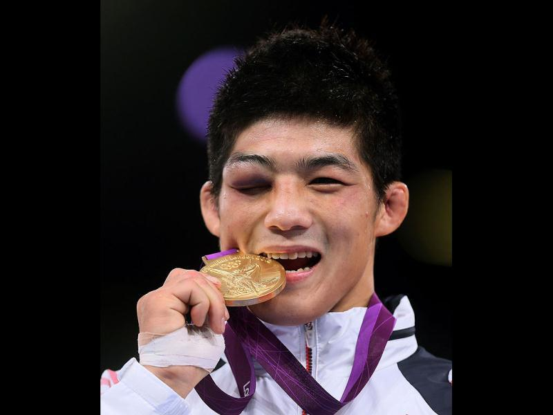 South Korea's Kim Hyeonwoo winner of the gold medal of 66kg Greco Roman Wrestling of the London 2012 Olympic Games bites his medal as he poses on the podium at the Excel Centre in London. AFP/Marwan Naamani