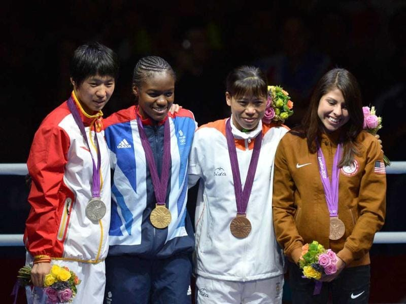 Gold medalist Britain's Nicola Adams (2D-L), silver medalist China's Cancan Ren, bronze medalists Marlene Esparza from the US and India's Chungneijang Mery Kom Hmangte celebrate on the podium of the the women's boxing Flyweight final of the 2012 London Olympic Games at the ExCel Arena in London. AFP/Alberto Pizzoli