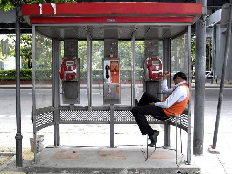 A Thai worker takes a break at a public telephone booth in Bangkok, Thailand. (AP Photo)