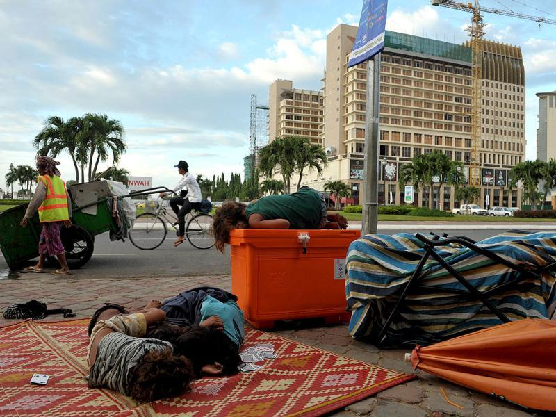 Cambodian children sleep on a street sidewalk in front of a casino and hotel in Phnom Penh. (AFP Photo)