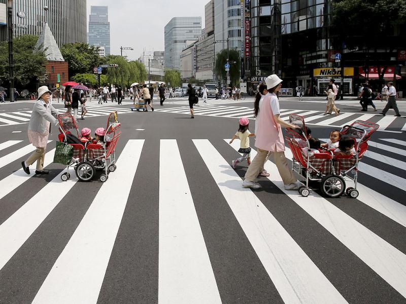 Teachers push carts with kindergarten children on board in Tokyo. (AP Photo)