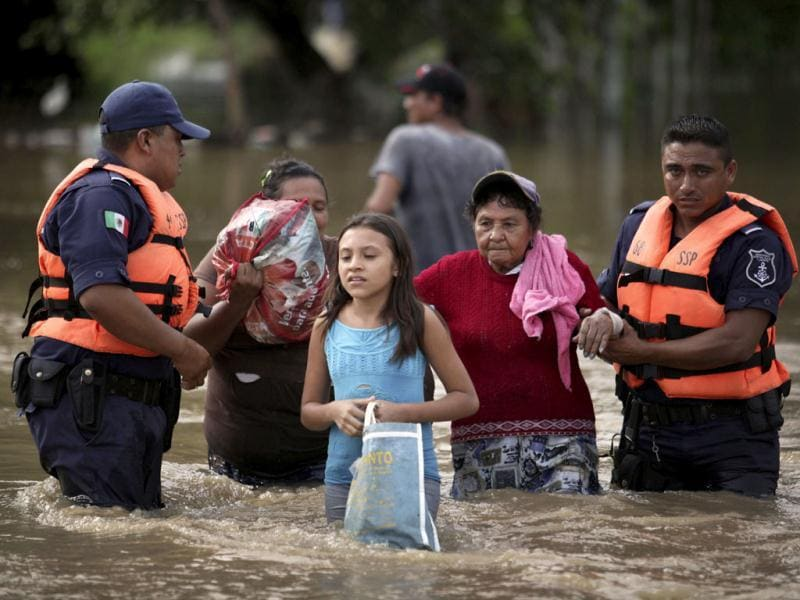 State police evacuate residents after the Jamapa River overflowed in the town of Jamapa, Mexico. Ernesto weakened to a tropical depression as it moved inland Friday, killing seven people and dumping rains in the mountains of Mexico's flood-prone southern Gulf region. AP Photo/Felix Marquez
