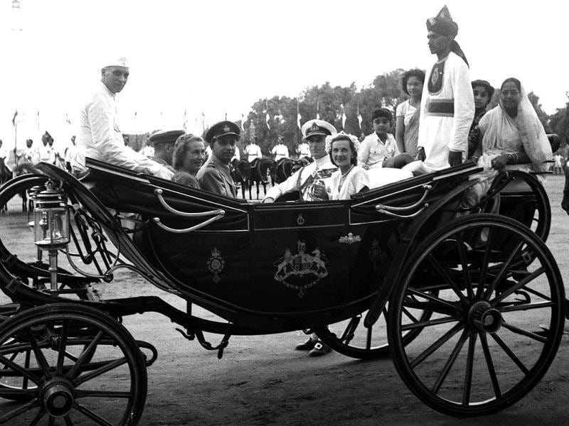 Lord and Lady Mountbatten, centre right, ride in a coach with Prime Minister Jawaharlal Nehru, seated on canopy at extreme left, at India's Independence Day celebrations in New Delhi, Aug. 15, 1947. At right are three women and a small boy saved by the Mountbattens from the crowd of a quarter of a million who broke up the Independence Day military parade. (AP Photo/Kelly)